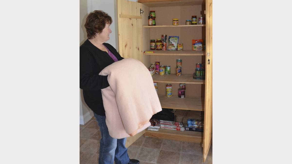 STOCKS ARE LOW: Jodie's Place coordinator Roxanne Shettler inspects the cupboard at the women's refuge. Blankets are also needed.